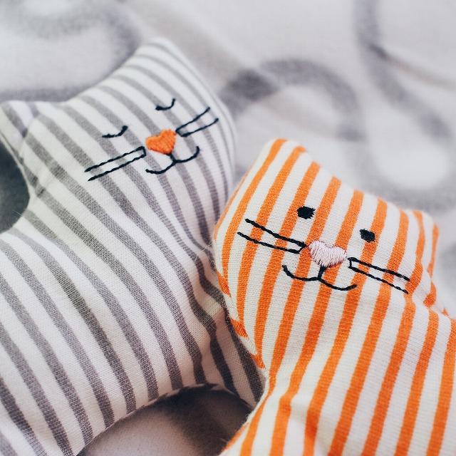 グレーとオレンジのしましまの猫型おもちゃのアップ写真。鼻の刺繍がハートでかわいいです。