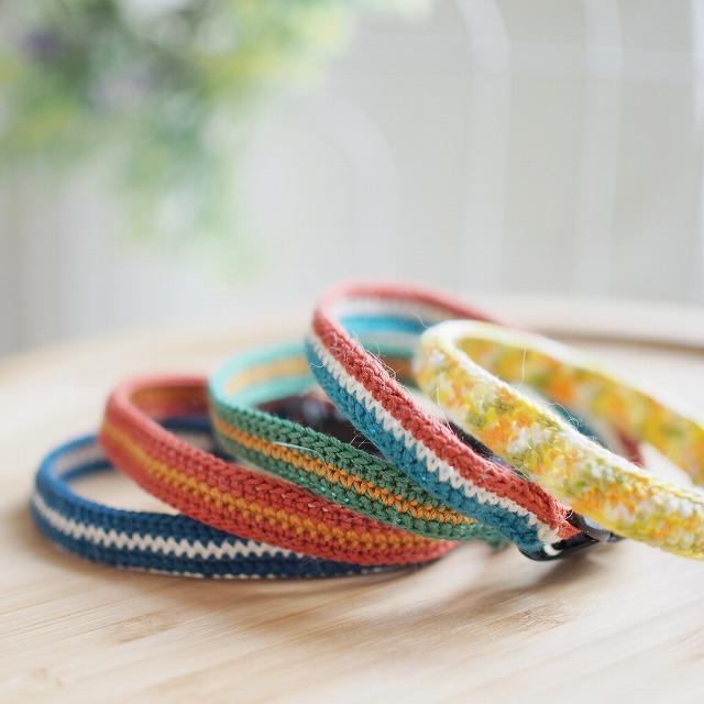 かぎ針編みで編んだ猫の首輪5つ。青に白のライン、赤に黄色のライン、緑に黄色のライン、赤白青のトリコロールカラー、黄色系マルチカラー。