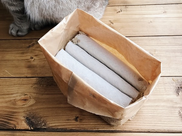 紙袋を開けたところ。中には白い紙に包まれた謎の塊が